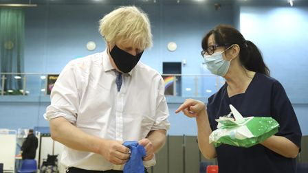 Prime minister Boris Johnson speaks with health worker Wendy Warren as he puts on a pair of medical