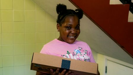 At the entrance to her apartment building, Shakayla Smith-Gayle proudly holds her new laptop deliver