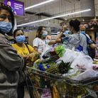 Shoppers wearing face masks with a cart full of food supplies wait in line to pay at a supermarket c