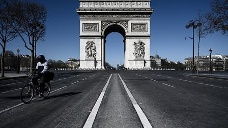 A man rides his bicycle past the Arc de Triomphe in Paris, France, with the city in lockdown to stop