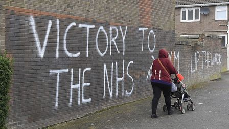A woman walks past a message of support for the NHS in Londonderry, as the UK continues in lockdown