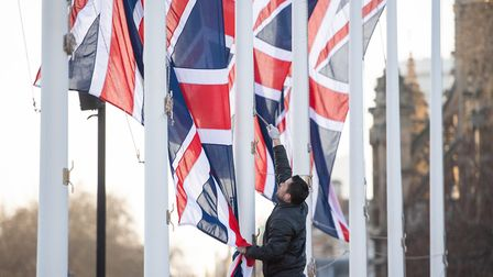 A worker removes Union flags from flagpoles in Parliament Square, London, following events to mark t