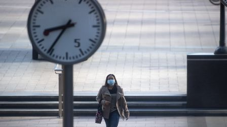 A woman wearing a protective face mask walks in Canary Wharf, London during rush hour, after Prime M