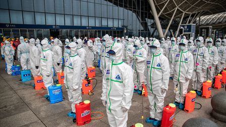 Staff stand to attention as they prepare to spray disinfectant at Wuhan Railway Station in China's c
