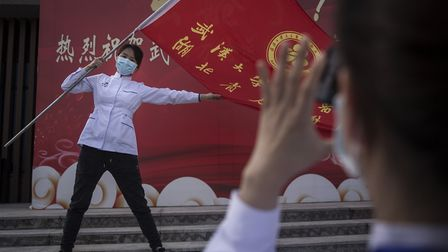 A medical professional holds a flag while posing for photos as Wuchang Fang Cang makeshift hospital