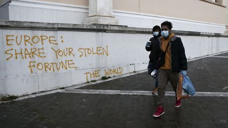 Two migrants from Sri Lanka with protective masks pass by a graffiti against European Union on the b