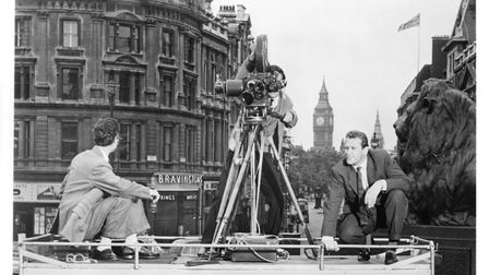 Edward Judd asks the newsreel cameraman if he can join them on top of the van in a scene from the fi