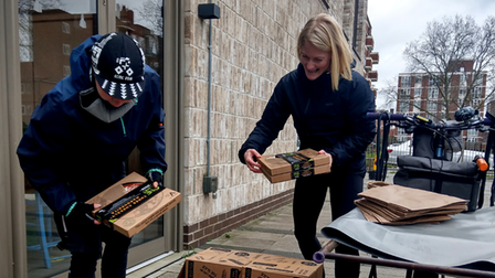 People staking pizza boxes for delivery.