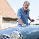 Portrait Of Mature Man Polishing Restored Classic Sports Car Outdoors At Home