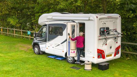 Person going into a camper van parked on a site