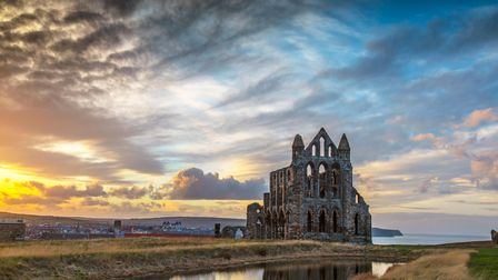 Landscape image showing the ruins of Whitby Abbey reflected in a pond in front of the abbey taken in
