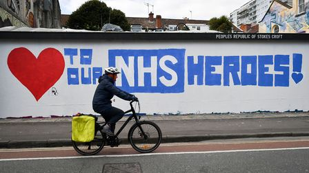A cyclist passes street art in Stokes Croft, Bristol, as the UK enters the second week of lockdown d