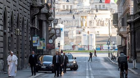 Pope Francis walks in a desert Via Del Corso, as he leaves the church of San Marcello on the Corso,