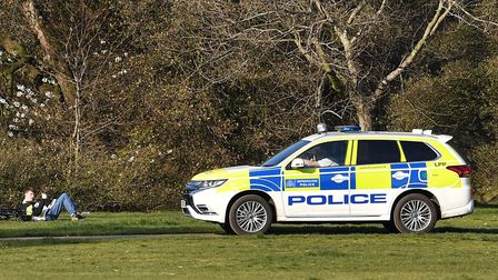 A police officer in a vehicle speaks to a man resting on the grass in Greenwich Park in London after
