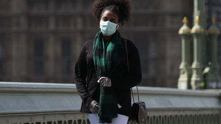 A passer-by wears a face mask on Westminster Bridge in London as the UK continues in lockdown to hel