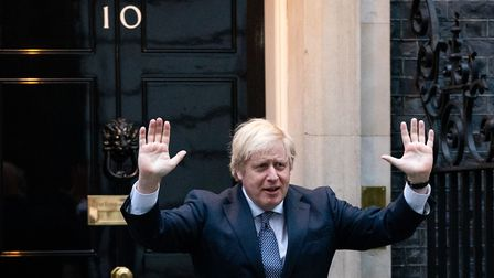 Prime Minister Boris Johnson stands outside 10 Downing Street as he joins in the applause to salute