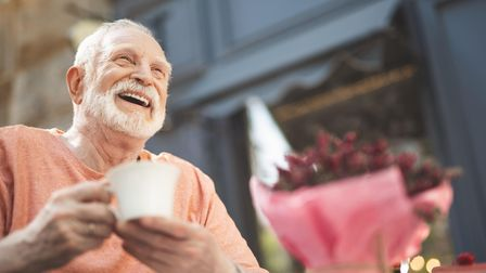 Low angle waist up portrait of delighted mature male sitting at table outside. He is holding cup of