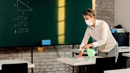 Elementary school teacher preparing classroom for children's arrival and disinfecting tables during