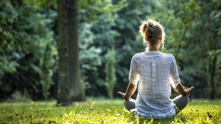 A woman meditates outside in nature