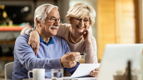 Happy senior couple going through home finances and using computer at home.