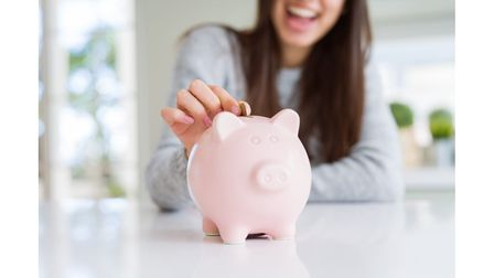 A woman smiles while putting money into a pig shaped money box