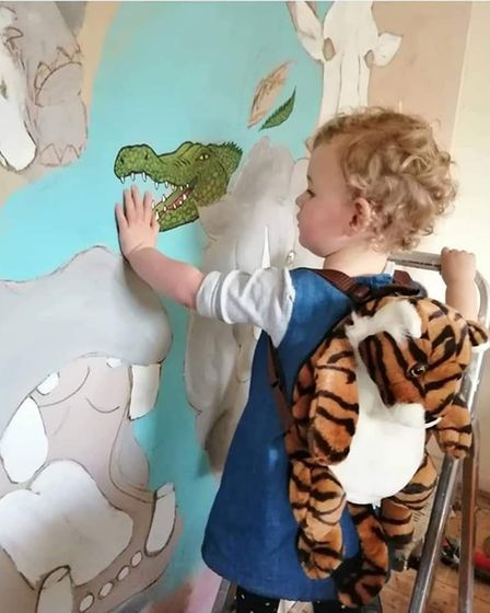 Freya showing her delight at her mum's work of the jungle mural by touching the crocodile.