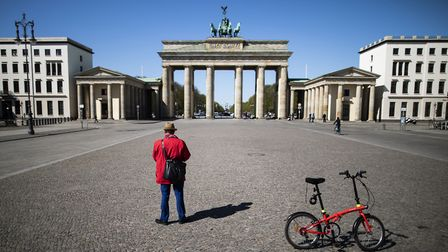 A single cyclist in front of the Brandenburg Gate in Berlin, Germany. (Photo by Florian Gaertner/Pho
