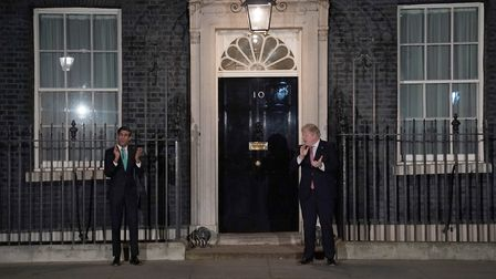 Chancellor Rishi Sunak and Prime Minister Boris Johnson applauding outside 10 Downing Street in a ge