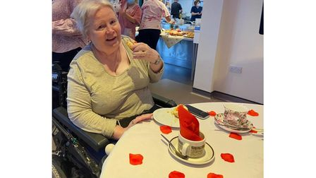 Picture of woman tucking into cream tea