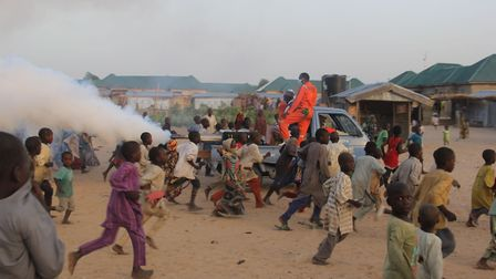 Children playfully run away from a fumigation machine mounted on the back of a pick up used in a dis