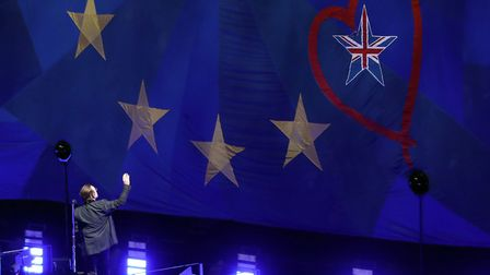 U2's Bono waves to a giant EU flag, with one star as the Union Flag, at the o2 Arena in London, duri