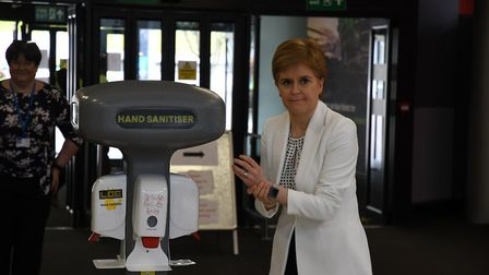 First minister Nicola Sturgeon washes her hands as she arrives for a visit to the NHS Louisa Jordan