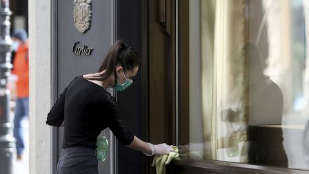 A woman wearing a protective mask cleans a shop window in Vienna, Austria. Smaller Austrian shops ma