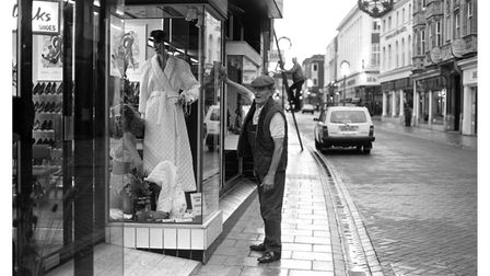 Cleaning the windows at Grimwades shop front in Westgate Street.