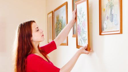 woman in red hanging the art pictures on wall at home