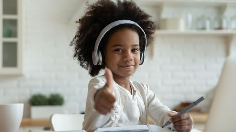 African girl in headphones enjoy e-learn sit at table showing thumbs up recommend e-study easy and i