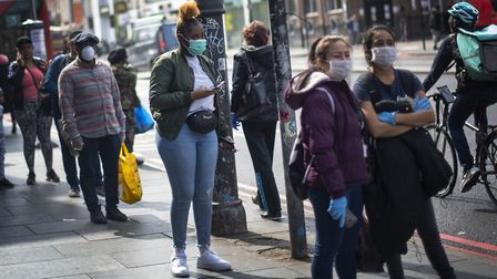 People wearing protective face masks wait in line for a supermarket in Brixton, South London, as the