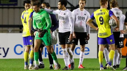 Torquay United keeper Shaun MacDonald heads for the dressing room after being shown a red card durin