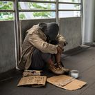 Sad Homeless old man or beggar head down and sit on city walk. Poverty with depression feeling in wi