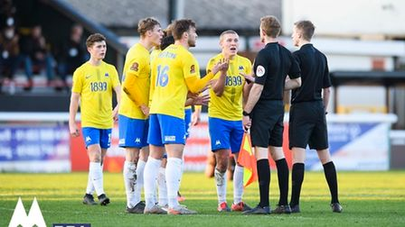 A furious Torquay United team confront the referee after Billy Waters of Torquay United is denied a