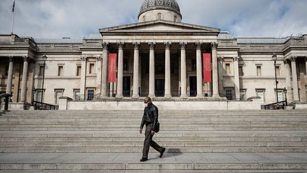 A man wearing a protective face-mask walks through a deserted Trafalgar Square in London, England. T
