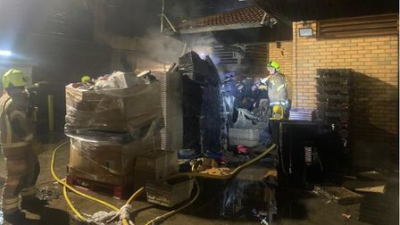 Firefighters among pallets and cardboard boxes outside a superstore in Tollgate Road, Beckton.
