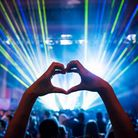 Green and blue strobe lighting shines across a music festival crowd. Two hands formed in the shape of a heart are...