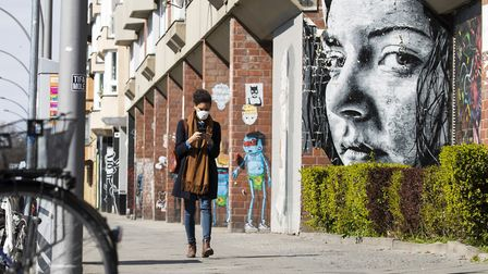 A young woman wearing a protective mask looks at her smartphone while passing by a grafitti represen