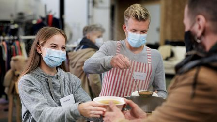 Volunteers serving hot soup for ill and homeless in community charity donation center, food bank and