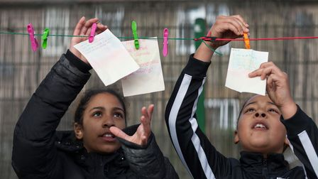 Children hang notes on a washing line.