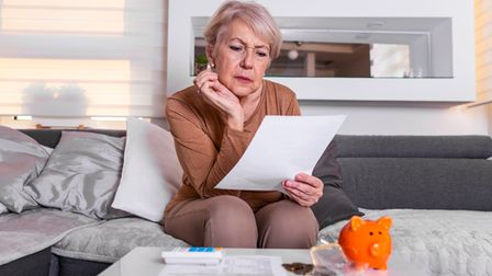 Senior woman doing finances at home. Senior woman with calculator and counting euro money at home. B