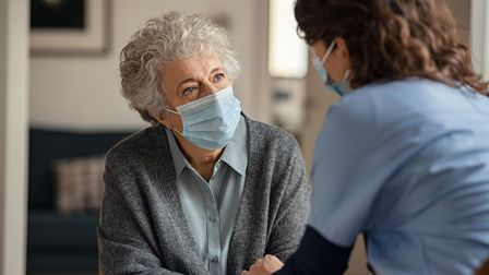 Elderly woman talking with a doctor while holding hands at home and wearing face protective mask. Wo