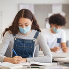 High school student taking notes from book while wearing face mask due to coronavirus emergency. You