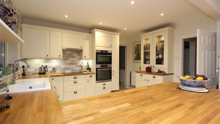 The modern kitchen of the property for sale by Debbie Fortune in Clevedon Road Tickenham has wooden worktops, cream units...